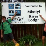 Kim van Kets Standing alongside the Mbotyi River Lodge Sign