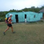 Kim van Kets running through a rural village in teh Transkei